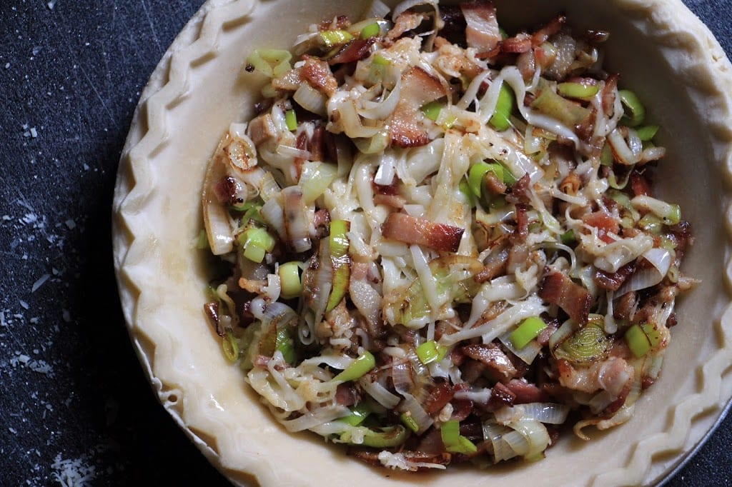 Fill the pie shell with the mixed leeks, bacon, and cheeses