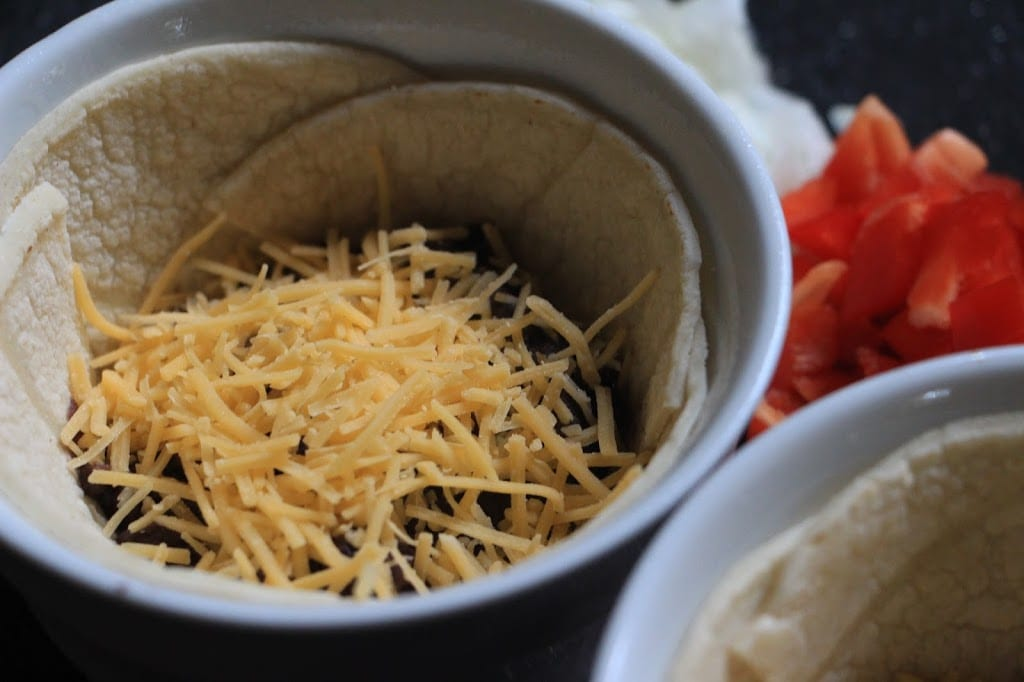 Fold the tortillas to form a bowl and add the beans and cheese