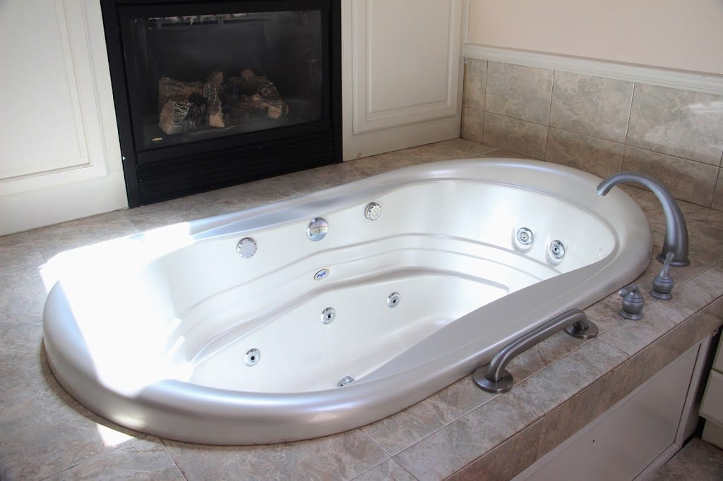 Jacuzzi tub for two beside the fireplace in Tropical Cottage