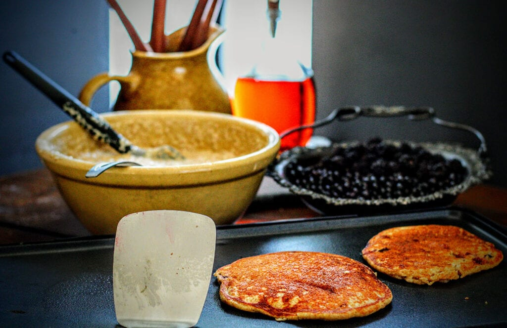 Scoop a half cup of batter onto a griddle or skillet for each pancake, top with huckleberries, then flip after bubbles form at the edges.
