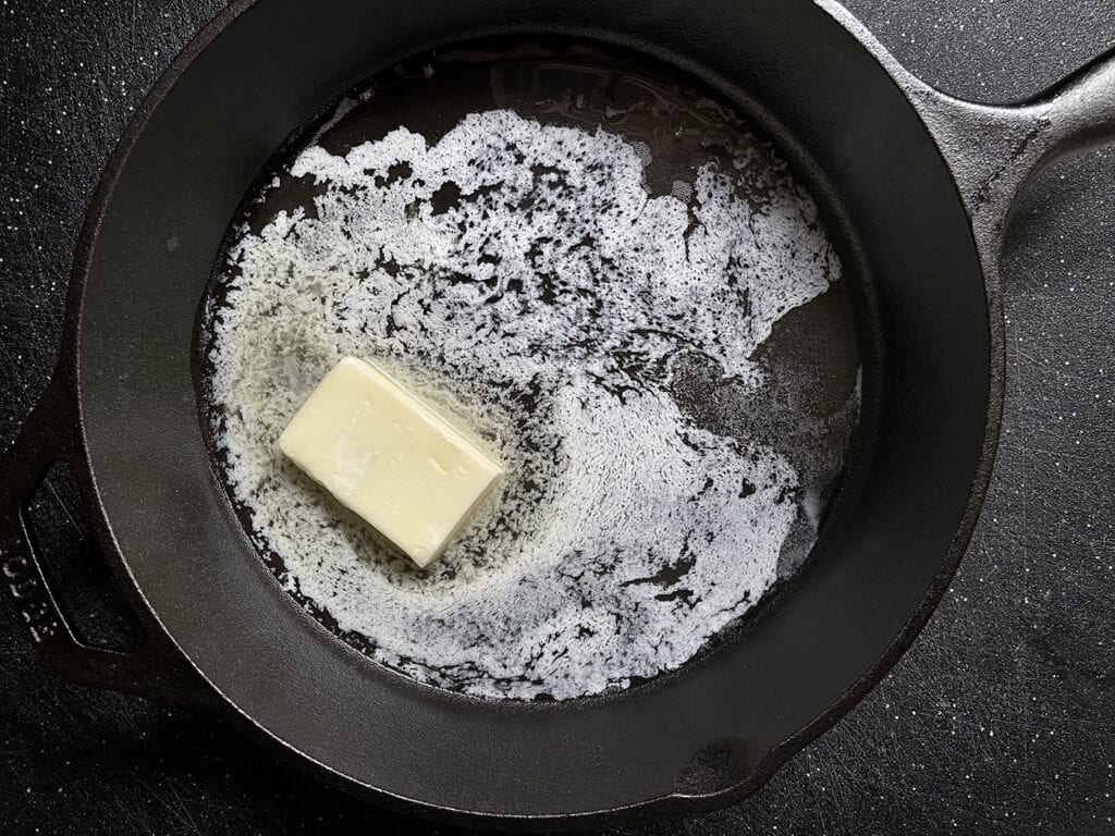Melt butter in a skillet for Tahoma Meadow's Mökki Pannukakku